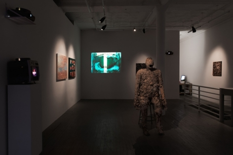 A photograph of the interior of the gallery. There is a video on the back wall with blue abstract patterns. In the middle of the room is a bronze figurative sculpture. Throughout the room we see 3 other large flat works installed on the wall and spot-lit.