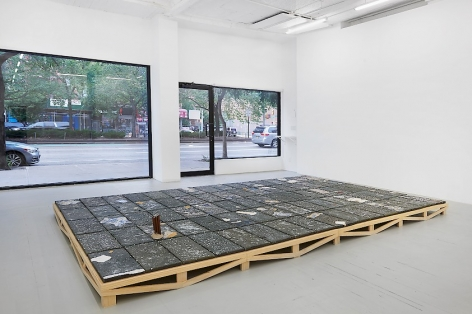 An installation image of Kahlil Robert Irving's large black clay tile artwork, installed on the floor on a wooden pedestal, with the windows of the gallery in the distance