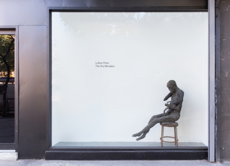 A photograph of the exterior of the gallery, which hosts a bronze figurative sculpture on a chair in the front window space. There is also the title of the exhibition in black letters on a white wall.