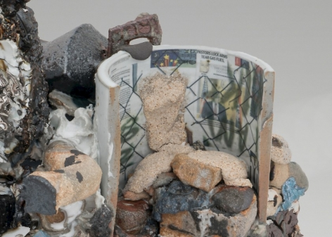 A detail of a mixed stoneware sculpture that introduces us to decals on the backside of a circular shape. There is a chainlink fence overlay, and we see newspaper press clips collaged together. There are also varies textures of clay in black, beige, silver, and white.