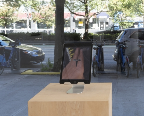 an iPAD on a stand placed on a pedestal. The iPAD has a still from the video. The image shows a person holding a smart phone