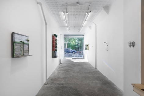 A view of the whole gallery from the back of the room. At the front is the large square window. On the left wall are 2 sculptural facades of buildings; on the right walls (starting closest to the viewer) is a grey fence out of paper, a streetlamp.