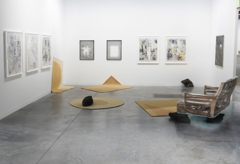 A photograph of the gallery's booth at an art fair, which includes 3 framed works on the left wall, 4 framed works on the back wall, and one wall on the right wall. There are 4 rugs on the ground, 2 of which go up the wall. There is also one wooden couch on the floor.