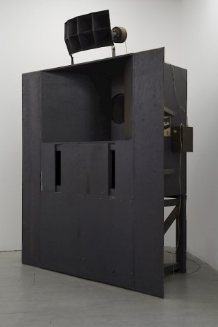 A photograph of the speaker component of this sculpture. It is painted black and functions as the speaker in the room. This is a side profile of the structure.