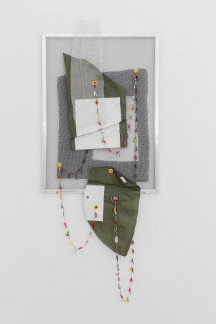 A mixed media collage. There is a silver frame that holds a traditional window screen. Upon that screen are pieces of fabric, fishing lures hung on a string, and iron-on areas.