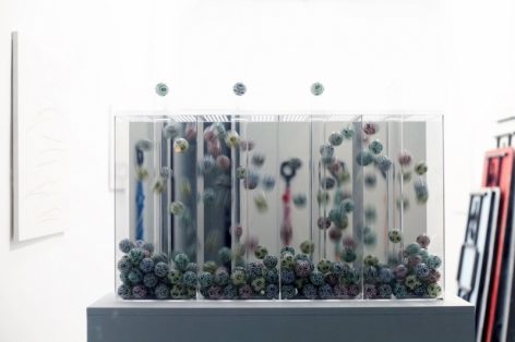 A close up of the vitrine with multi-colored balls in the air.