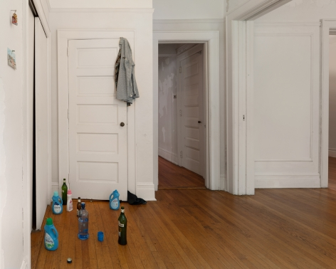 A photograph of the left side of the installation with detergent and liquor bottles on the ground, a shirt over a door in the background