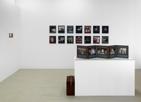 "A photograph of the front quadrant of the gallery: Dayanita Singh's unfurled book-object on a pedestal is in the foreground; the background has 2 rows of Dayanita's ""Museum of chance"" book-objects; at left on the temporary wall is a black and white photograph by Guibert."