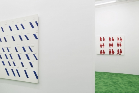 A photograph of another view of the back gallery. At left is the white and blue artwork on the front gallery's back wall; on the right is a view into the back gallery with a white canvas with pairs of bathroom figures in red.
