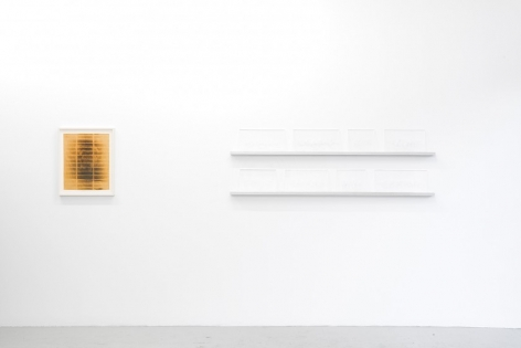 A view of one framed print of a grid pattern burned into yellow paper at left; at right are two white shelves, each of which hold 4 pieces of glass sheets of varying sizes.