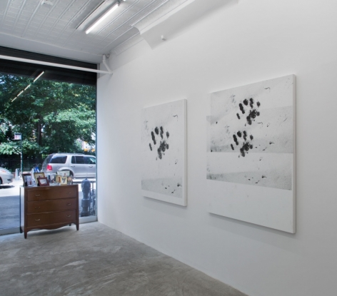 A photograph of the front of the gallery: at right are two white paintings with black cat paws; near the window we see a wooden dresser with illegible photographs upon it.