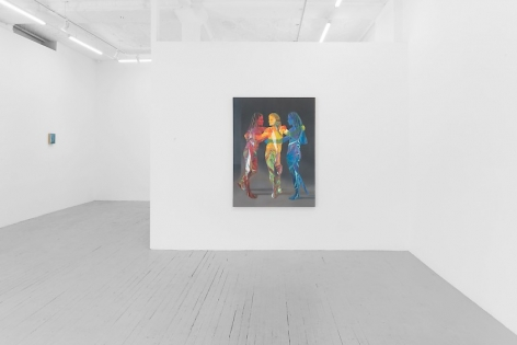 A photograph of a large painting on the gallery's temporary wall depicting 3 standing figures painted in red, yellow and blue. There is a small painting on the left wall opposite the temporary wall, too small to make out details.