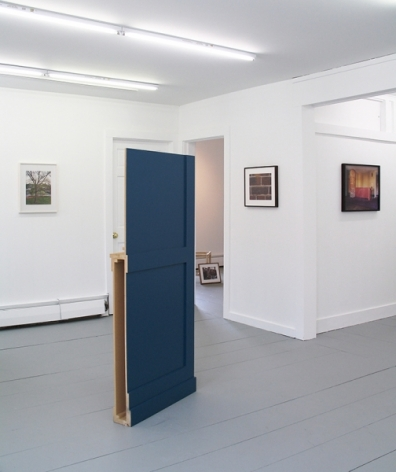 A photograph of a sculpture installed on the floor, painted blue. There are 3 photographs on 3 walls in the background