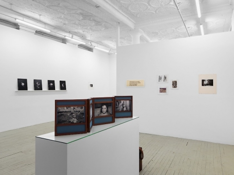A photograph of the gallery. We are standing behind Dayanita Singh's unfurled book-object upon a pedestal. In the background are 5 works on the temporary wall at right, and a series of 4 black prints by Pradeep Dalal on the left side. In the distance at left is a photograph by Guibert that is illegible.