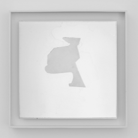 An artwork framed in white. On a white ground, there is an abstract shape that is centrally situated in a square composition. The shape is gray.
