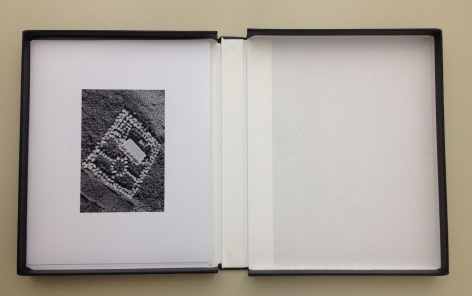 A photograph of an open binder with a single black and white photograph on top.