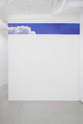 A swatch of vinyl with a photoshopped image of clouds on a blue sky, installed in a single line near the top of a wall in the back office of the gallery