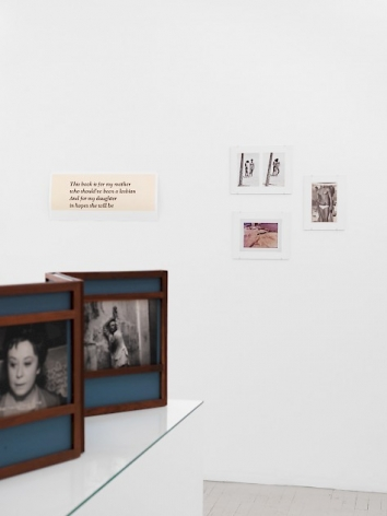 A photograph that details 4 works on the temporary wall. The work at left has 4 lines of text. To the right are three color photographs hung in a loose triangle.