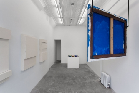 A photograph of the gallery from the front of the space. There are 3 works on the wall, one hanging from the ceiling, and one on a pedestal in the back