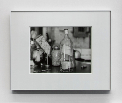 A black and white photograph of a bottle on a table amid other kitchen accessories.