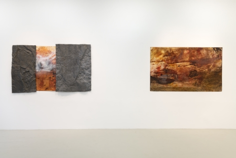 two paintings hanging on the wall where both works have orange brown and white colors in gestures that look like tumultuous sea scapes and the painting on the left has textured metal components attached to the surface