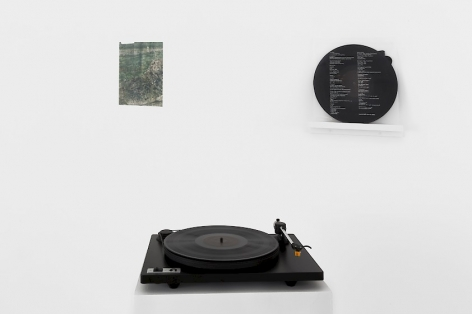 A photograph of a black record player in the foreground, a record poised on the wall in the background, and an unframed print to the left of the record on the wall.