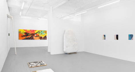 A wide photograph of the gallery. Starting at right: three enamel paintings on steel, one large sculpture leaning against the temporary wall in the gallery, one large horizontal painting on the back wall, one small illegible painting on the left wall with a large sculpture next to it, and one print installed on the ground at left.
