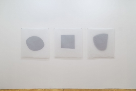 A photograph of 3 tracing paper works with shapes in the center, installed on the wall