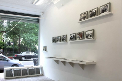 A photograph of the front gallery window with 3 platforms for photographs leaning against the wall, and one shelf of the book laid out (not visible)