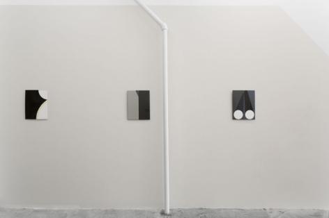 Three enamel paintings on a grey wall