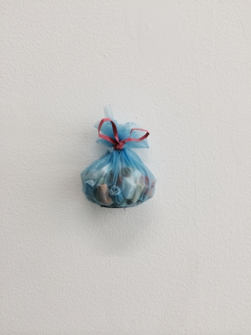 A small clear blue trash bag with miniature cans and bottle inside of it. The bag is hung on the wall.