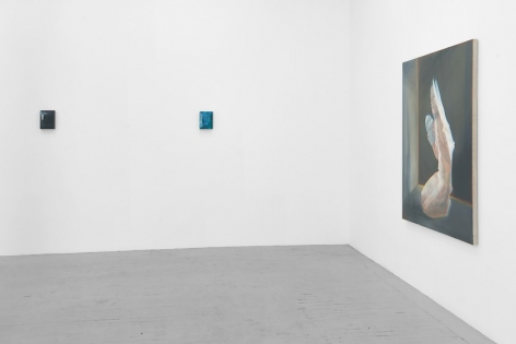 A photograph of 2 small paintings on the far wall, and one large painting on a close wall at right. The painting at right is of the kneeling naked female figure, seemingly made of cellophane.