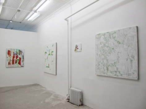 A photograph of 4 abstract painting on 2 walls: at the back wall, it is predominantly red.