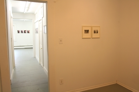 A photograph from the back room in the gallery with 2 small framed works, and a view of 4 works down at the other end of the hall