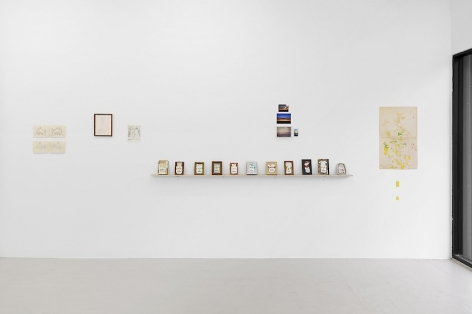 An installation view, on the wall is a sculpture made up of old cigarette cartons on a shelf, and 4 other drawings on paper without frames.