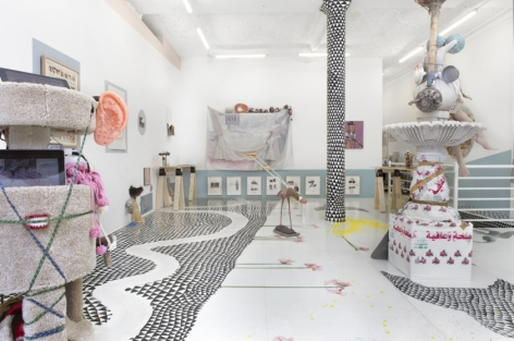 A photograph of the interior of the gallery. There is a site-specific installation with black triangles on the ground and flowers painted to be coming out of it. There are several mixed media sculptures installed on the ground. On the walls at more mixed-media works with the contents illegible. The pole is painted black and white with triangles.