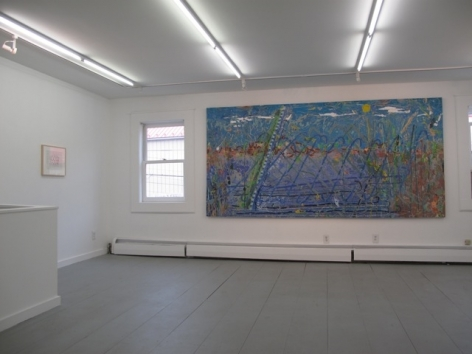 A photograph of the gallery with the large blue painting central, and a small illegible work at left on the wall