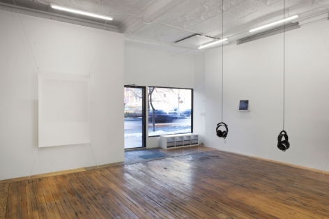A photograph of the interior of the gallery, with a view of the windows in the background. There are 2 sets of headphones hanging from the ceiling, and Tom Martin's piece at right in the background. At left is a screenprint stretched at 4 corners, off the wall.