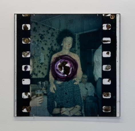 An enlarged film still with a woman in the center, and a hole burned in the center surrounded by purple ink.