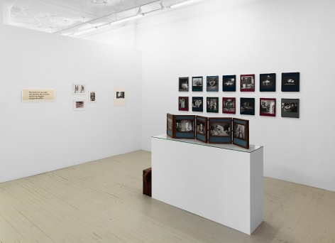 "A photograph of the front quadrant of the gallery: there is a pedestal with an unfurled photography book-object by Dayanita Singh and 2 row of Dayanita Singh's ""Museum of chance"" on the right wall; at the left temporary wall is a series of 5 artworks in varied sizes, hung salon-style."