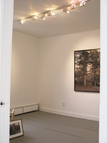 A photograph of 2 works in a small room: one is a photograph on the far wall, and one is on the ground in a frame