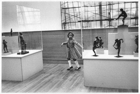A black-and-white photograph of a young Black girl dancing in a museum, where bronze sculptures are contorted within vitrines