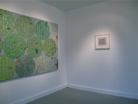 A photograph of a large green work at left and an abstract framed work at right.