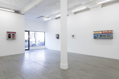 A photograph of the front half of the gallery. At left is a building facade, followed by the open gallery window with a view of the sidewalk. The 2 sculptures of building facades and one drawing are installed on the wall at left of the gallery's entrance.