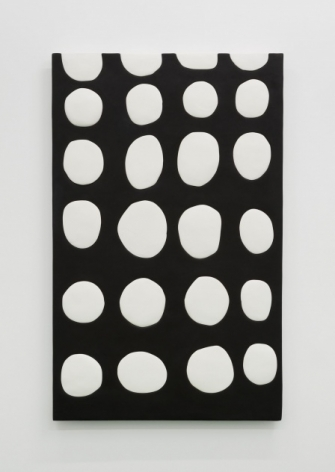 A black surface with four columns and 6 rows of white dots in similar but irregular sizes.