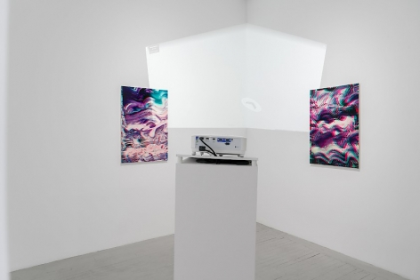 A straight-on view of 2 artworks situated around a corner in the gallery, with the back of the projector in the forefront. The light on the wall is a projection of the interior of the gallery via Google Maps.