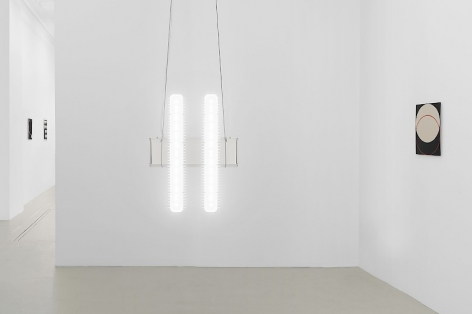 An installation view of the LED industrial light straight-on, with Ulrike Muller's enamel on steel work (2 circles interlacing) at right. To the left we see the entry way back to the main gallery.