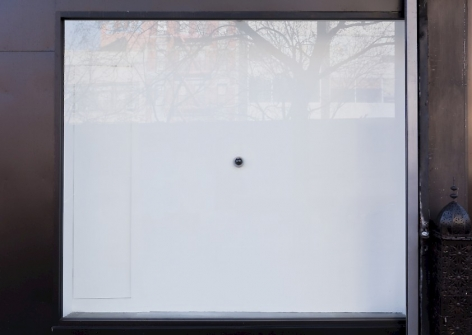 A photograph of the exterior of the gallery, which depicts a small camera situated on a white wall behind the glass of the gallery's facade.