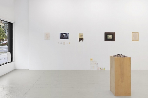 An installation view that includes small magazine clippings piled on a wooden pedestal at right, and 4 mixed-media works installed on the wall.