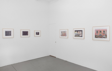 A photograph of the gallery around a corner. There are three black and white drawings on the left wall, and 3 color drawings on the right wall. All are framed in natural wood frames.